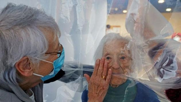 Family members stand on either side of the plastic sheet to interact.(REUTERS)