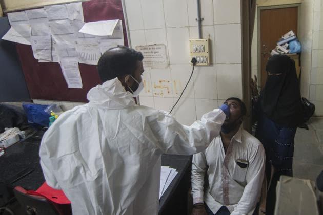 A health worker takes a swab test in Govandi on Saturday.(Pratik Chorge/HT Photo))