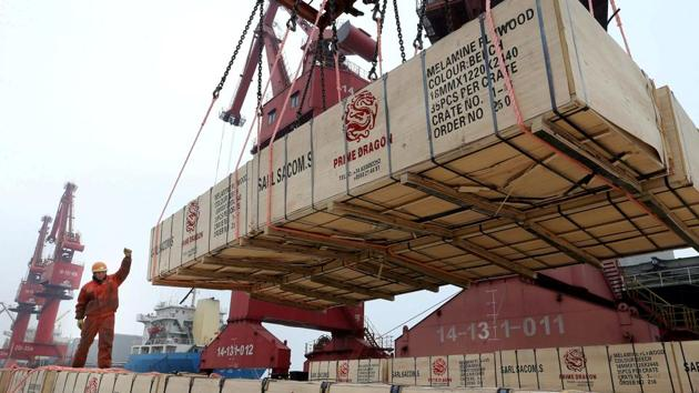 A worker gestures as a crane lifts goods for export onto a cargo vessel at a port in Lianyungang, Jiangsu province, China.(Reuters file)