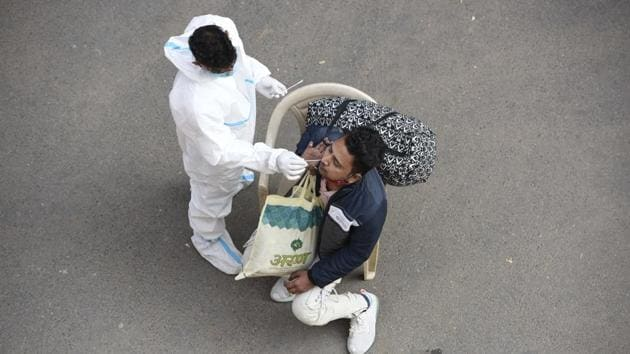 A medical worker collects a swab sample for coronavirus test at IFFCO Chowk, in Gurugram, on December 5.(HT file)