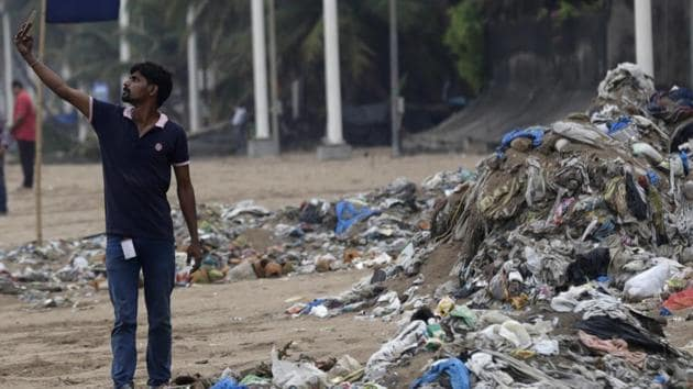 A man takes a selfie in front of a heap of garbage on the shores the Arabian Sea in Mumbai.(AP file)