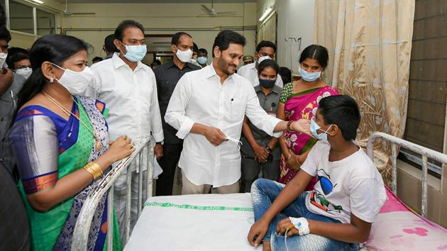 Andhra Pradesh chief minister YS Jagan Mohan Reddy meets patients who fell ill in Eluru town of Godavari district on Monday.(PTI Photo)