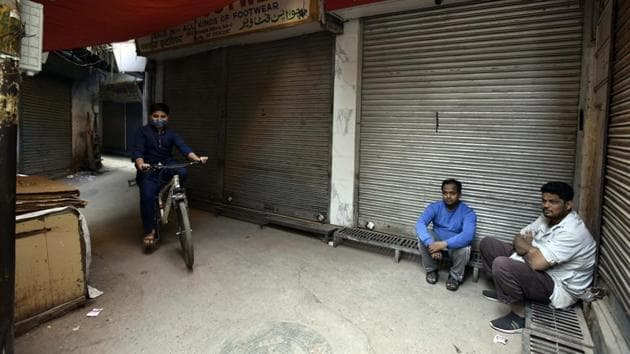 People sit in front of closed shops at Ballimaran market in the wake of Bharat Bandh called by protesting farmers against new farm laws, in New Delhi, India, on Tuesday, December 8, 2020.(Sanjeev Verma/HT photo)