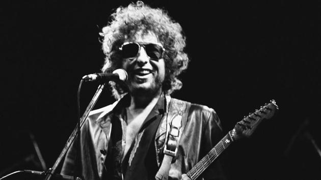 American singer Bob Dylan smiles as he performs during his show at the Colombes Olympic stadium in Colombes, France on June 24, 1981. Dylan's entire catalog of songs, which spans 60 years and is among the most prized next to that of the Beatles, is being acquired by Universal Music Publishing Group. The deal covers 600 song copyrights.(AP)