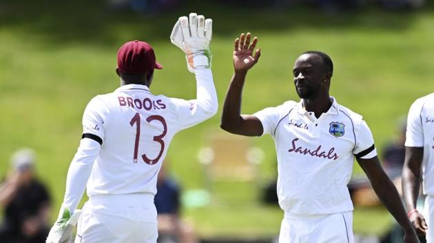 West Indies Kemar Roach, right, celebrates with Shamarh Brooks after taking the wicket of New Zealand's Henry Nicolls during play on day two of the first cricket test between the West Indies and New Zealand in Hamilton, New Zealand, Friday, Dec. 4, 2020.(AP)