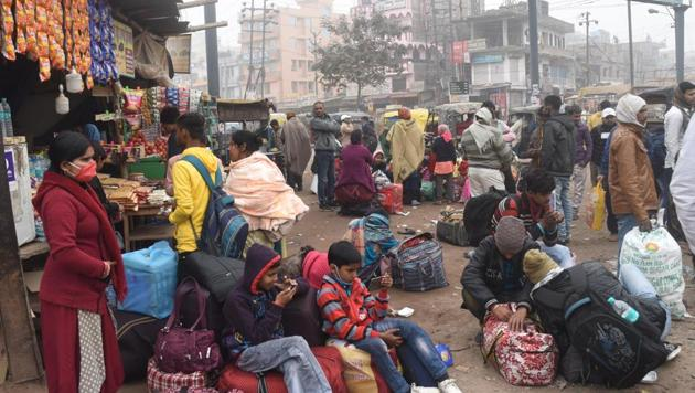 Passengers wait for alternate transport services after bus services were suspended at Patna's Mithapur bus stand on Tuesday in solidarity with farmers' call for Bharat Bandh against new farm laws.