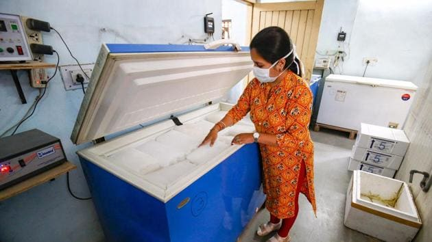 A medic checks the temperature of ice packs in a deep freezer at a Covid-19 vaccine storage facility in Ahmedabad.(PTI)