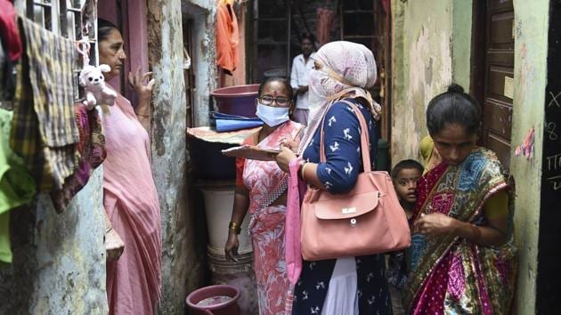 A health department worker interacts with residents during a door-to-door survey at Dharavi slum in Mumbai earlier this month.(PTI File Photo)