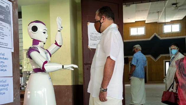 The robot named Sayabot greets a voter at a polling station in Kerala's Ernakulam .(HT PHOTO)