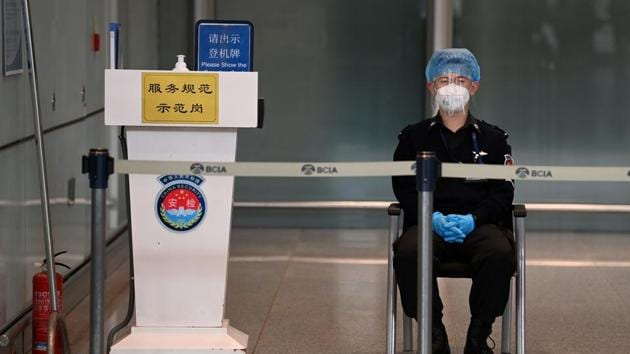 A security guard watches over the empty international arrivals channel at Beijing airport on November 6.(AFP)
