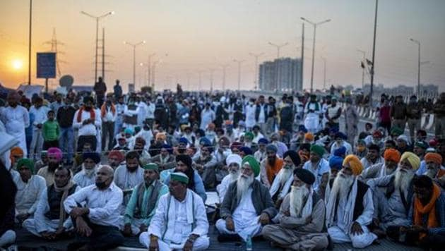Farmers listen to a speaker on the middle of an expressway at the site of a protest against new farm laws at the Delhi-Uttar Pradesh state border.(AP)