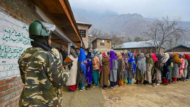 A security personnel stands guard as residents wait in a queue to cast their votes during the fourth phase of District Development Council (DDC) elections, at Laar in Ganderbal district.(PTI)