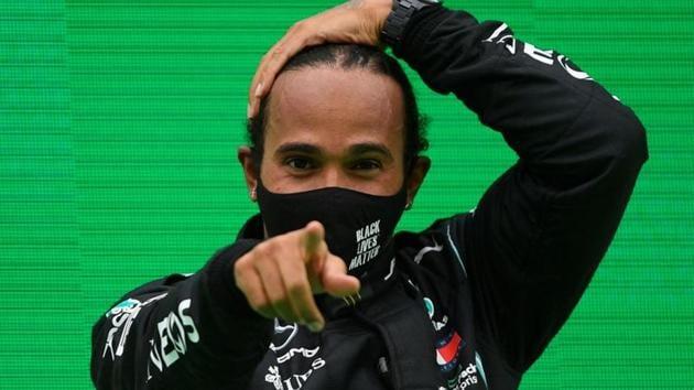 Mercedes' Lewis Hamilton celebrates winning the race on the podium.(Pool via REUTERS)