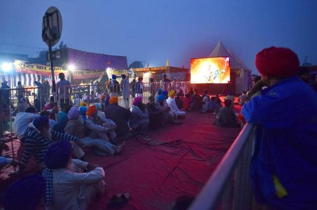 Farmer viewing a video playing on a large screen while camped at Singhu Border against the new farm laws, near New Delhi.(Sanchit Khanna / Hindustan Times)