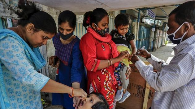 A health worker administers polio vaccine to a child as another marks a child on her finger in Kolkata, India.(AP)