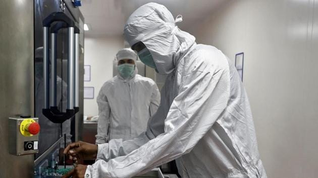 An employee in personal protective equipment (PPE) removes vials of AstraZeneca's COVISHIELD, coronavirus disease (COVID-19) vaccine from a visual inspection machine inside a lab at Serum Institute of India, Pune.(REUTERS)