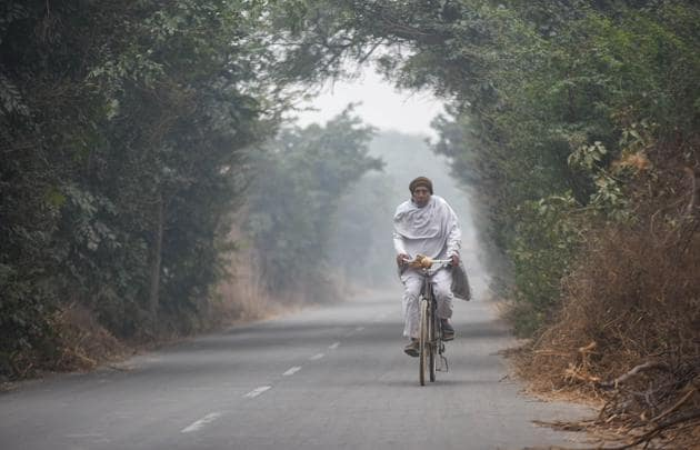 A cyclist seen on a foggy afternoon at Singhu border near Delhi on Saturday.(Amal Ks/HT Photo)