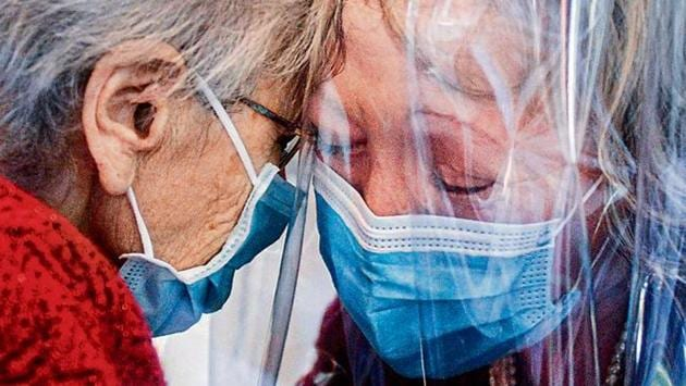 """A resident (L) of the Domenico Sartor nursing home in Castelfranco Veneto, near Venice, hugs her visiting daughter through a plastic screen in a so-called """"Hug Room"""" amid the new coronavirus pandemic.(AFP)"""