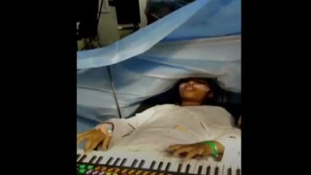 The image shows the girl playing the keyboard during surgery.(Hindustan Times)