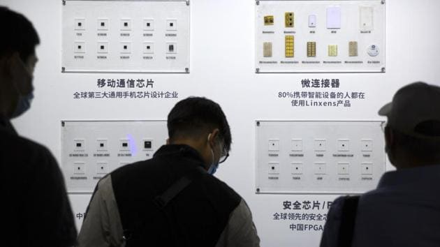 People look at semiconductors on display from the Tsinghua Unigroup at the China Beijing International High Tech Expo in Beijing. A major government-backed player in China's technology race, the company defaulted on its loans.(AP File Photo)