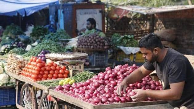 A vegetable vendor awaits customers while arranging onions in his cart at a market in Prayagraj.(AP photo)