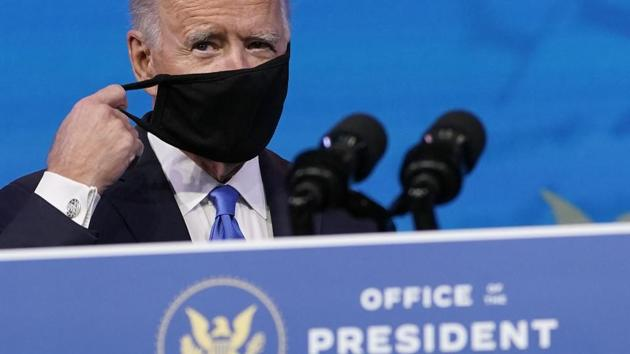 President-elect Joe Biden removes his mask as he arrives to speak after the Electoral College formally elected him as president, Monday at The Queen theater in Wilmington, Delaware.(AP)