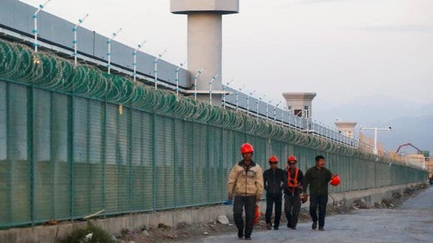 People walk by the perimeter fence of what is officially known as a vocational skills education centre in Dabancheng in Xinjiang Uighur Autonomous Region, China.(REUTERS/ FILE)