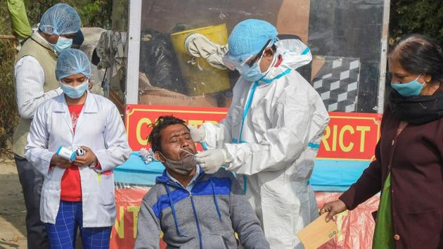 A healthcare worker, wearing protective gear, collects swab sample for Covid-19 test, in New Delhi on Tuesday.(PTI Photo)