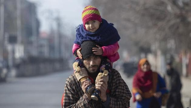 A Kashmiri man carries his child on shoulders and walks with other family members towards a bus terminal on a cold day in Srinagar.(AP)