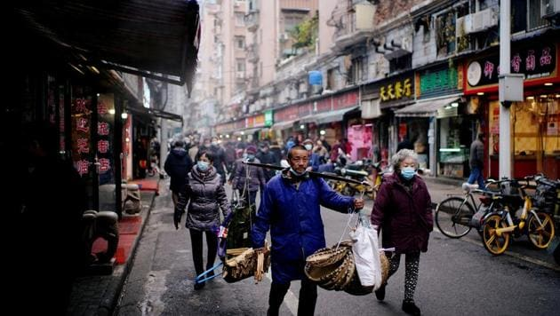 People wearing protective masks walk at a street market almost a year after the start of the coronavirus disease (Covid-19) outbreak, in Wuhan, Hubei province, China.(REUTERS)
