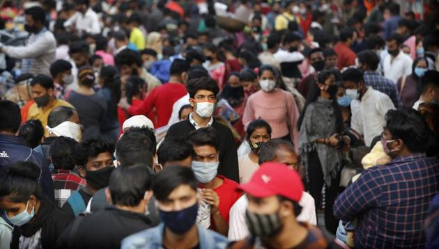 Indians wearing face masks as a precaution against the coronavirus shop at a market in New Delhi, India.(AP)