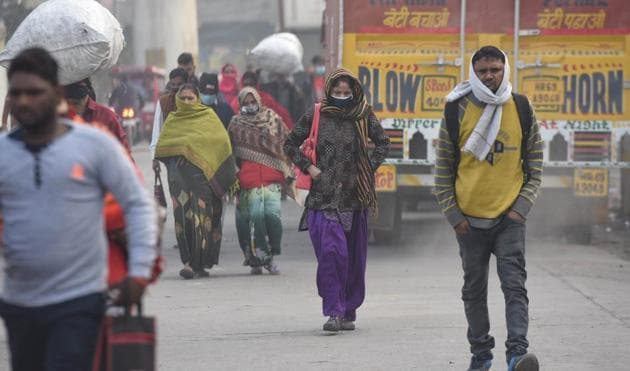 Commuters wear face masks and winter clothes on a cold morning at Azadpur in New Delhi on Tuesday.(Sanchit Khanna /HT PHOTO)