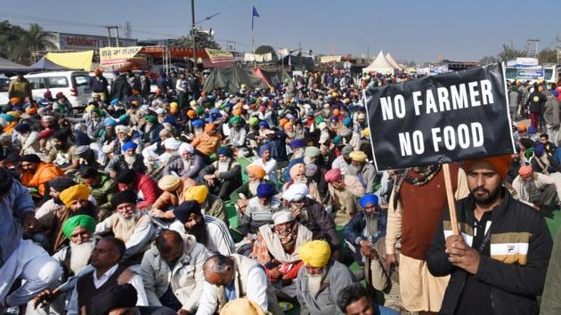 A farmer holds a banner during a protest against the new farm laws, at Singhu (Delhi-Haryana border) near New Delhi on Wednesday.(Ajay Aggarwal /HT PHOTO)