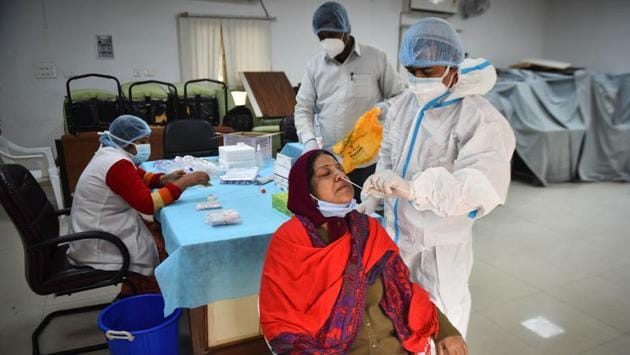 A health worker collects a swab sample to test for coronavirus infection in New Delhi on December 17. India has recorded the world's second-highest number of infections behind the United States, but numbers have dipped steadily since hitting a peak in September. Daily cases were below 30,000 for the fifth straight day on December 18. (Sanchit Khanna / HT Photo)