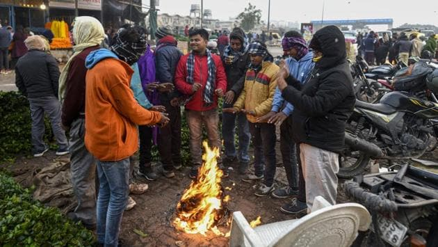 People warm themselves around a bonfire made using gunny bags on a cold winter morning at Ghazipur vegetable market in New Delhi on December 17. At 3,13,831 as on December 18, India's active cases are less than 1/30th the amount of total recoveries made so far, the health ministry said. (Biplov Bhuyan / HT Photo)