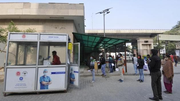 People queue outside a collection kiosk as a health worker collects swab samples at Sector 30 District Hospital in Noida on December 15. As cumulative cases of the respiratory disease close in on 10 million, the addition of 31,087 new discharges in the previous 24 hours has also taken the number of total recoveries past 9.5 million. (Sunil Ghosh / HT Photo)