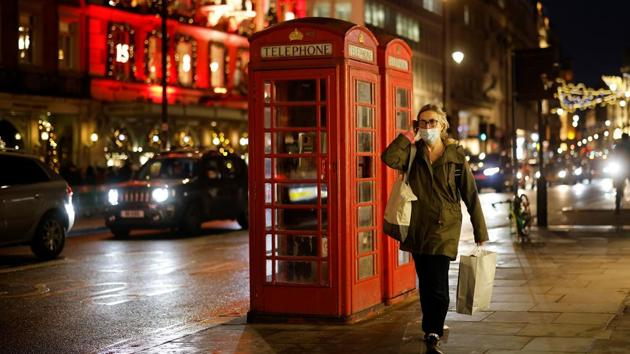 A pedestrian walks past Red Telephone boxes in London on December 19, 2020.(AFP)