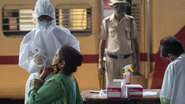A health care worker collects swab sample of the passengers at Dadar station in Mumbai on Friday.(Pratik Chorge/HT Photo)