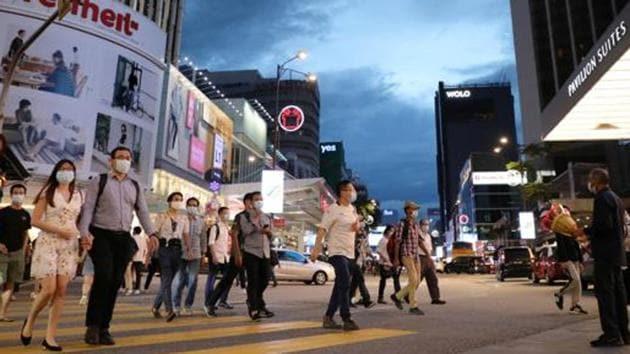 People wearing protective masks cross a street, amid the coronavirus disease (Covid-19) outbreak, in Kuala Lumpur, Malaysia.(REUTERS)