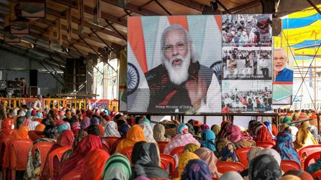 Farmers watch the live telecast of Prime Minister Narendra Modi's speech on a screen during 'Kisan Mahasammelan', in Raisen, Friday.(PTI Photo)