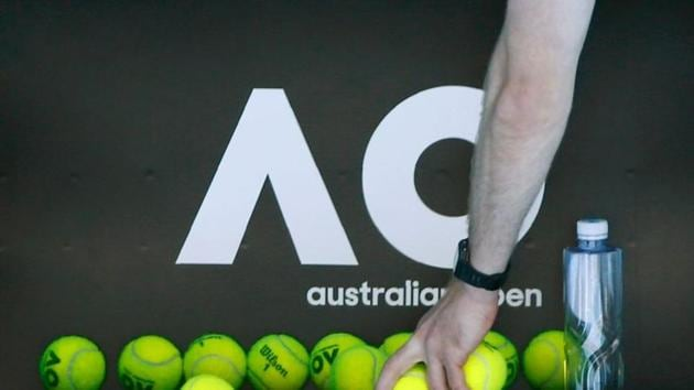 Tennis - Australian Open - Melbourne, Australia, January 14, 2018. A person picks up tennis balls in front of the Australian Open logo before the tennis tournament. REUTERS/Thomas Peter/Files(REUTERS)