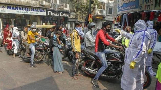 People wait in queues for their thermal scanning before entering a market in Ahmedabad in this file photo.(PTI)