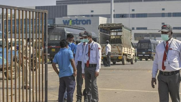 Security personnel stand guard outside Wistron Infocomm Manufacturing India Pvt Ltd, where a section of workers went on a rampage at its facility manufacturing Apple iPhones and other products over non-payment of promised wage, at Narasapura area in Bengaluru, Sunday, Dec. 13, 2020.(PTI)