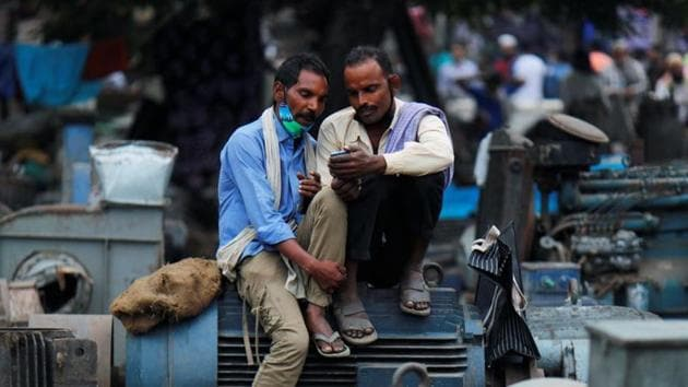 Men wearing protective face masks on their chins, amid the coronavirus disease outbreak, watch a video on a mobile phone as they sit at a second-hand motor parts market in the old quarters of Delhi.(REUTERS)
