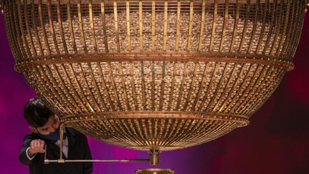 A ball bearing a ticket number falls from a giant drum at Madrid's Teatro Real opera house during Spain's bumper Christmas lottery draw known as El Gordo, or The Fat One, in Madrid, Spain.(AP)