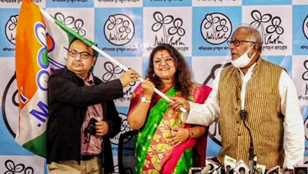Kolkata: Sujata Mondal (C), wife of BJP MP Saumitra Khan, holds the Trinamool Congress party flag after joining TMC in the presence of party MP Sougata Roy(R) and leader Kunal Ghosh, in Kolkata, Monday, Dec. 21, 2020.(PTI)