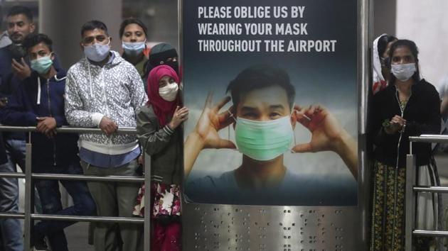 People wearing face masks as a precaution against the coronavirus wait for their relatives arriving from United Kingdom, at Chhatrapati Shivaji Maharaj International Airport in Mumbai.(AP)