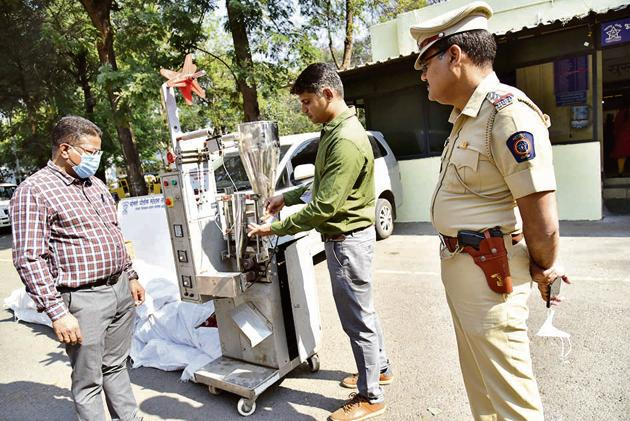 A police official demonstrates the functioning of the seized gutkha making machine in Bhosari.(HT PHOTO)