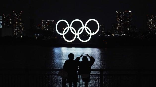 file photo of a man and a woman looking at the Olympic rings float in the water in the Odaiba section in Tokyo.(AP)