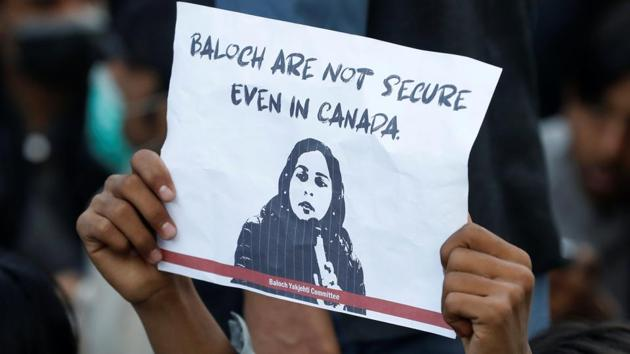 A person holds a placard to condemn the death of Karima Baloch, a Pakistani human rights activist living in Canada, who went missing and was found dead.(REUTERS)